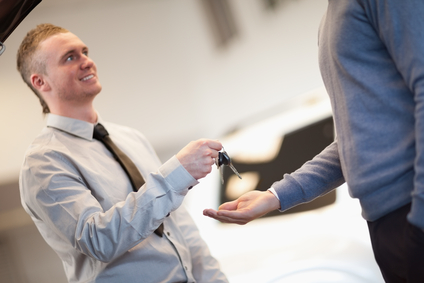 Smiling man giving keys ta a man in a car shop