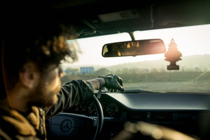 man inside a car with reflection on rear view mirror 730x487 at The certain challenges that come as a delivery driver