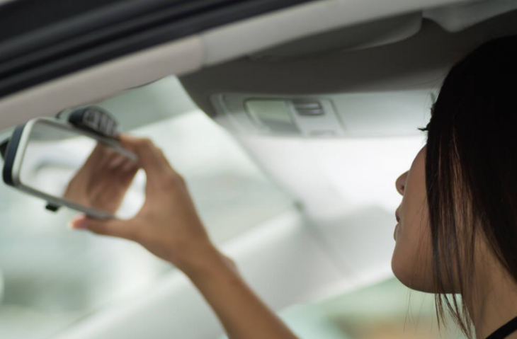 women adjusting car mirror 730x479 at 4 Driving Mistakes Every New Car Owner Must Avoid