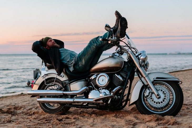 man laying on bike 730x487 at Tune in While Touring: 7 Best Podcasts for Motorcyclists